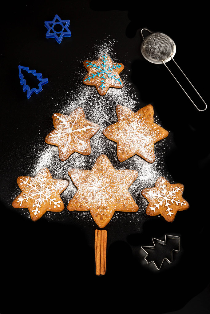 Gingerbread xmas tree with cookie cutters and strainer on black