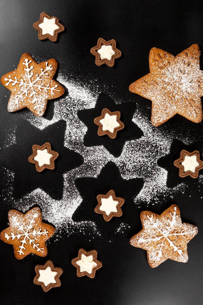 Top view of gingerbread snowflakes and cookies stars on dark background