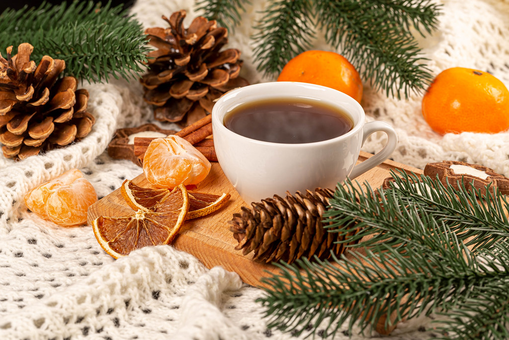 Cup of coffee on christmas background with tangerines and pine cones