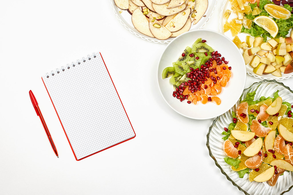 Plates of healthy salads with a blank notepad