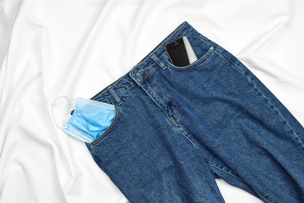 Jeans with a face mask and smartphone in the pocket