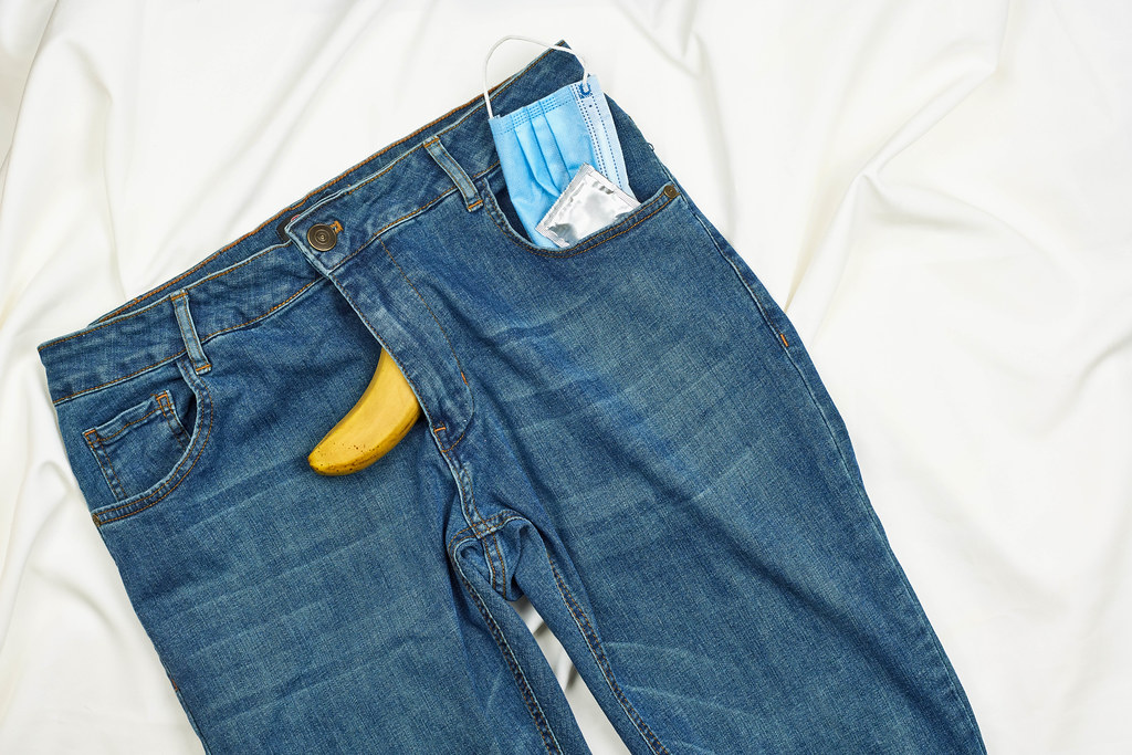 Face mask and condom in the pocket of jeans with banana