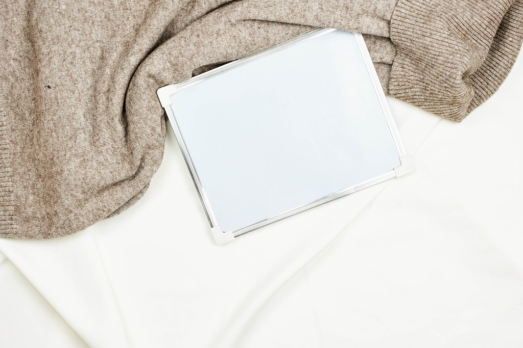 Warm sweater and whiteboard with copy space