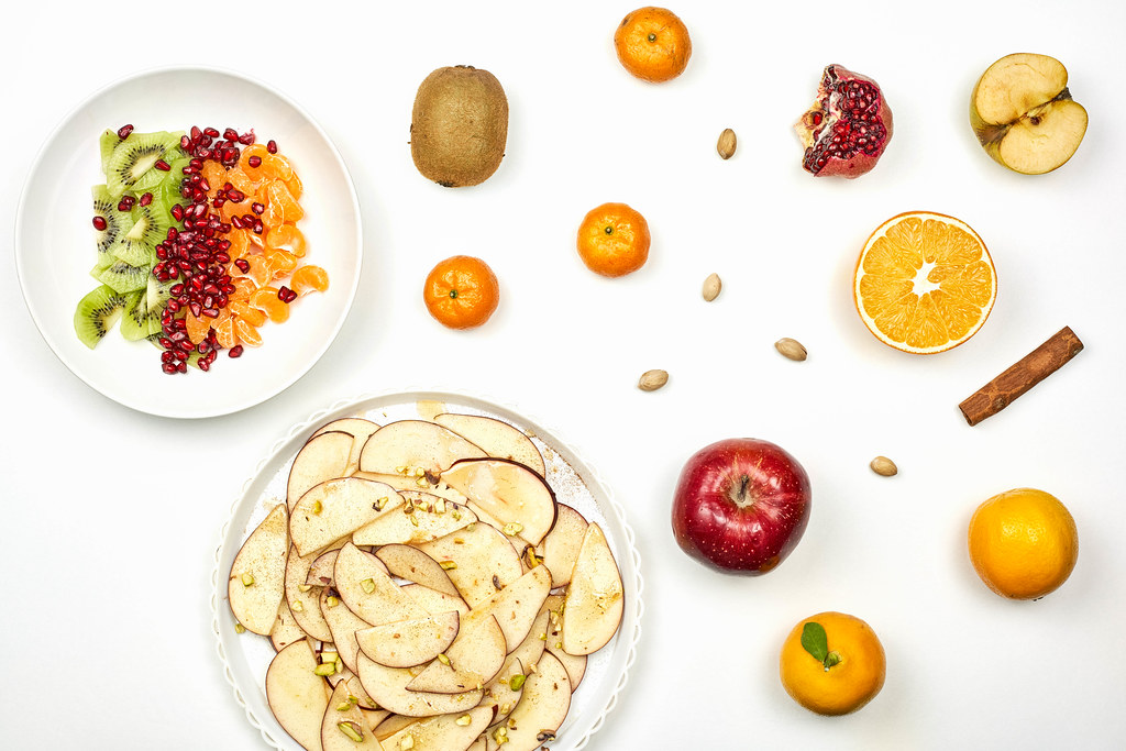 Sweet raw fruits and salads on white background