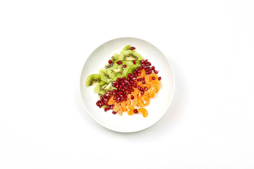 Kiwi, orange and pomegranate slices on the bowl