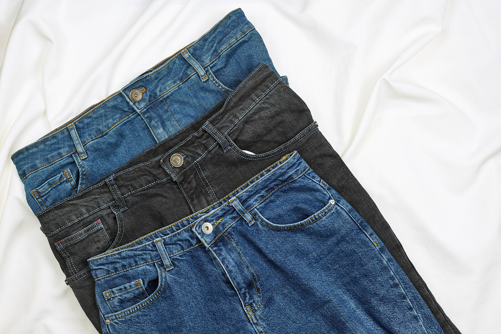 Three jeans trousers on white