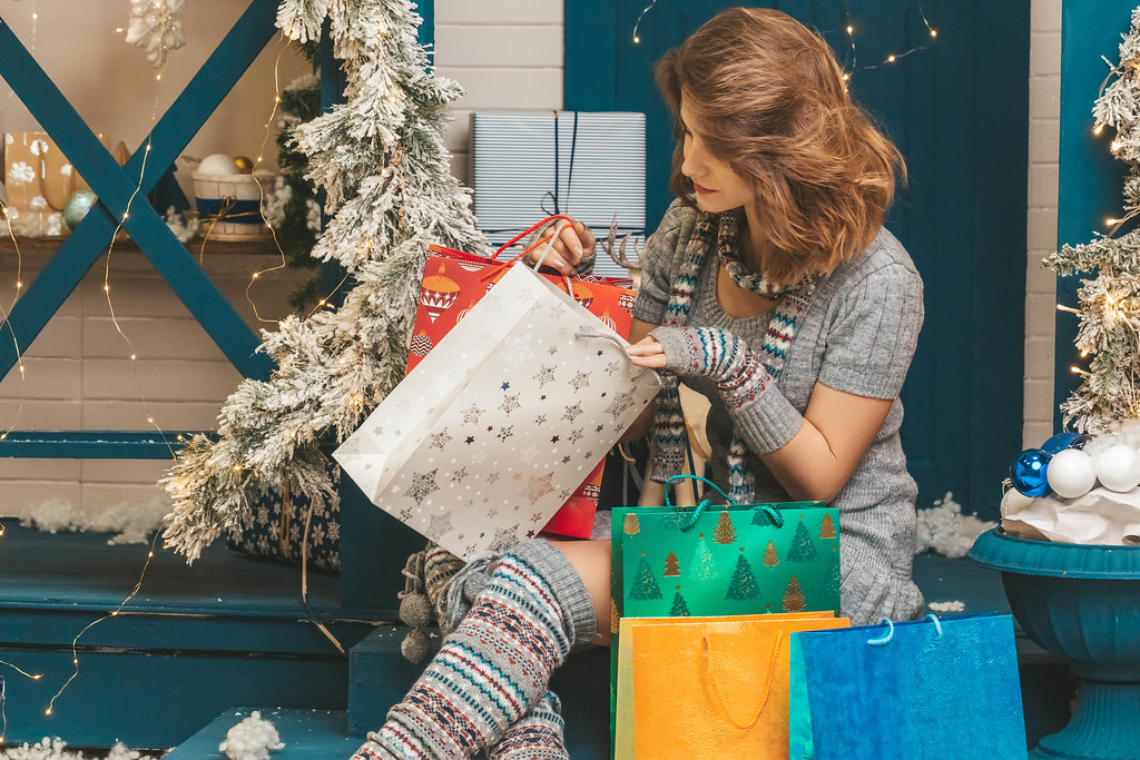 Girl peeks into a gift bag, the concept of gifts for the winter holidays