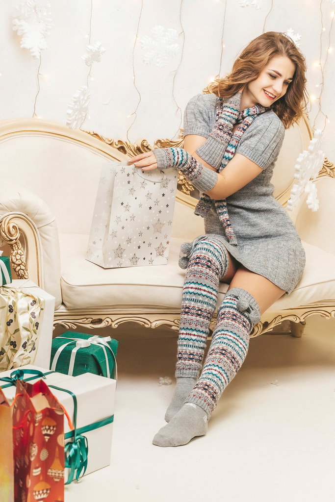 Girl with gift bag sitting on sofa in light decorated christmas living room
