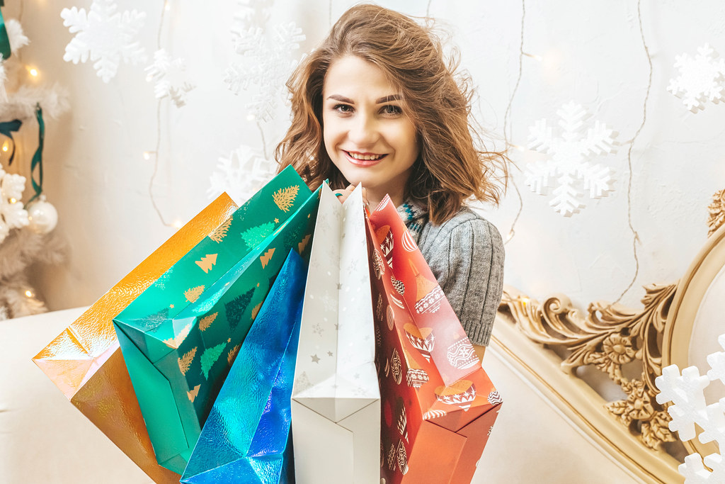 Close-up portrait of a young woman with colorful gift bags