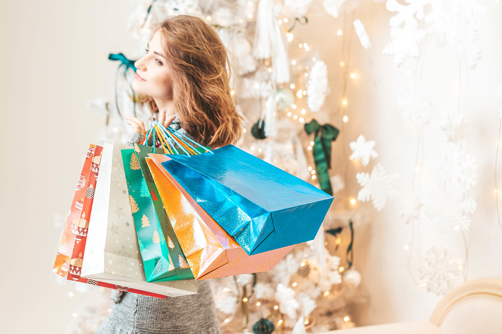 Young girl with gift bags in a light festive interior