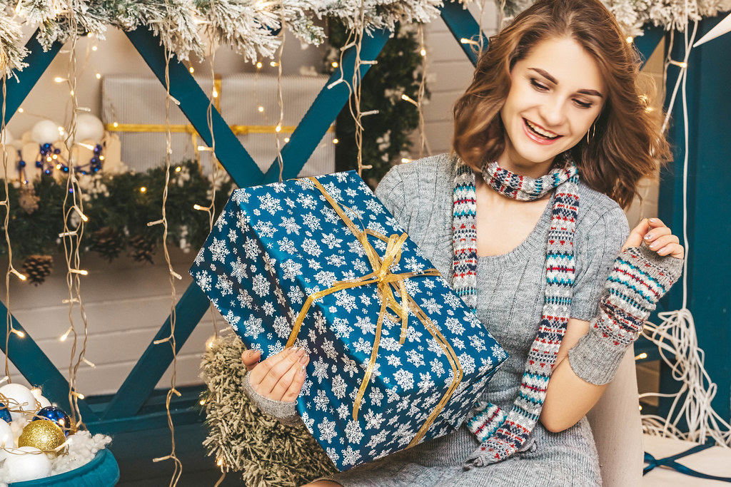 Concept of christmas surprise, gift in hand of happy girl