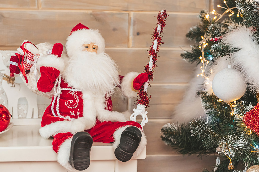 Santa claus toy in christmas interior with christmas tree