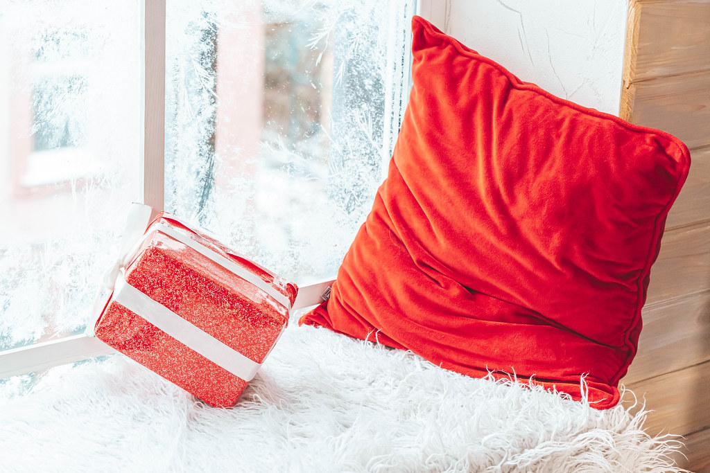 Gift and red pillow on the windowsill in winter