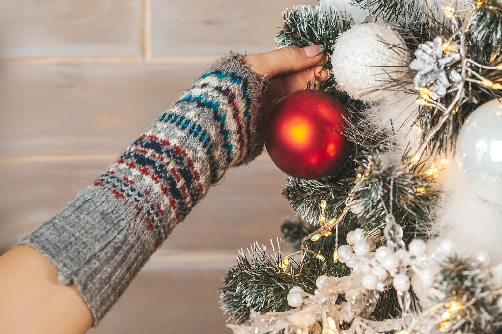 Close-up, hand hangs a red ball on the christmas tree