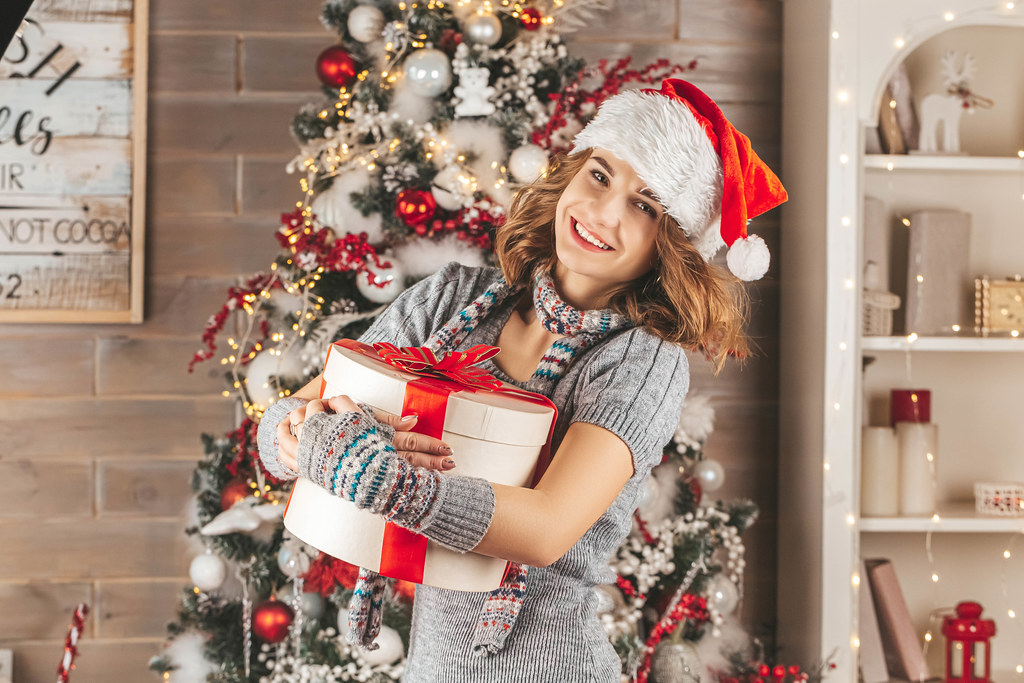 Happy girl hugging gift in christmas decorated room