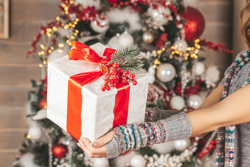 Beautifully decorated christmas gift with a red ribbon in the hands of a girl