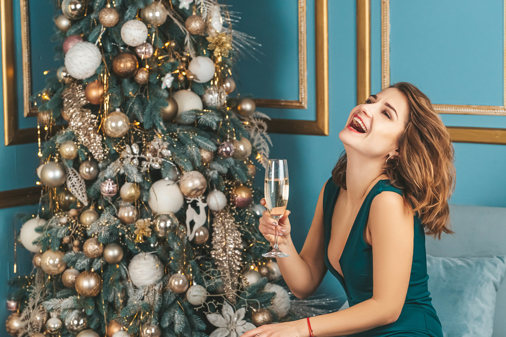 Festive new year background, a girl laughing with a glass of champagne near the christmas tree