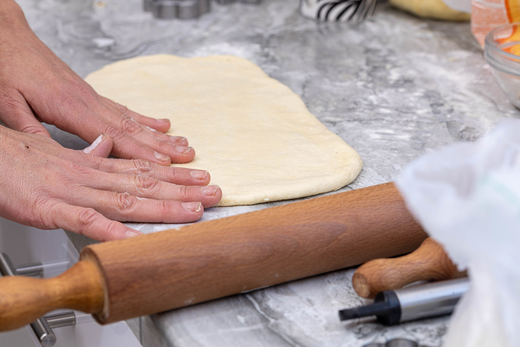 Raw Dough on the table with hands on it and rolling pin