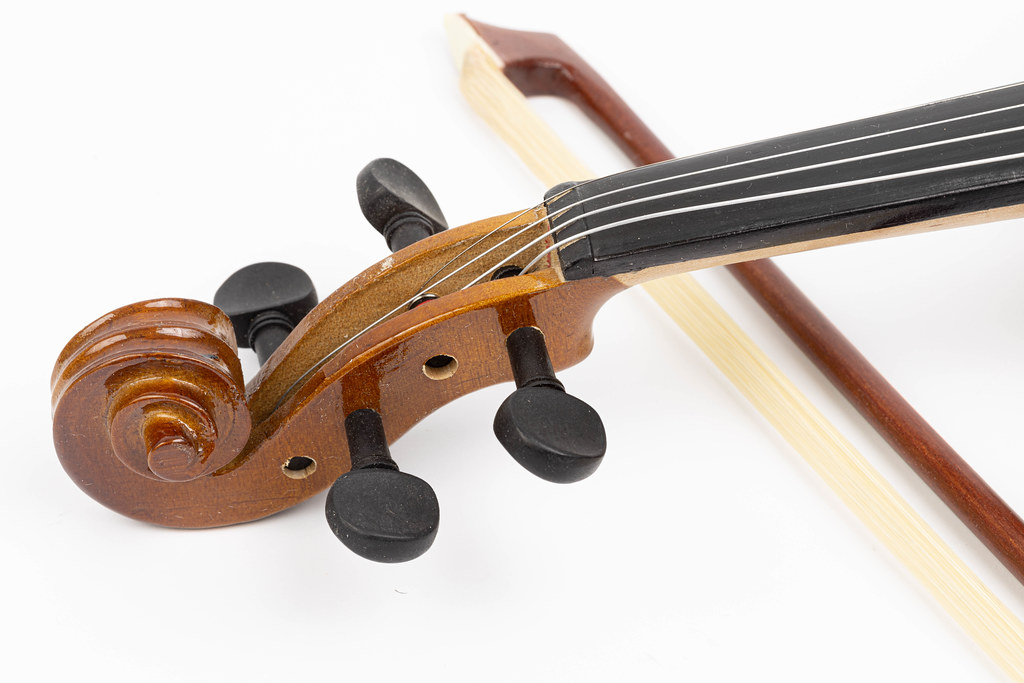 Violin Scroll with Tuning Pegs and Fiddle Bow in the background