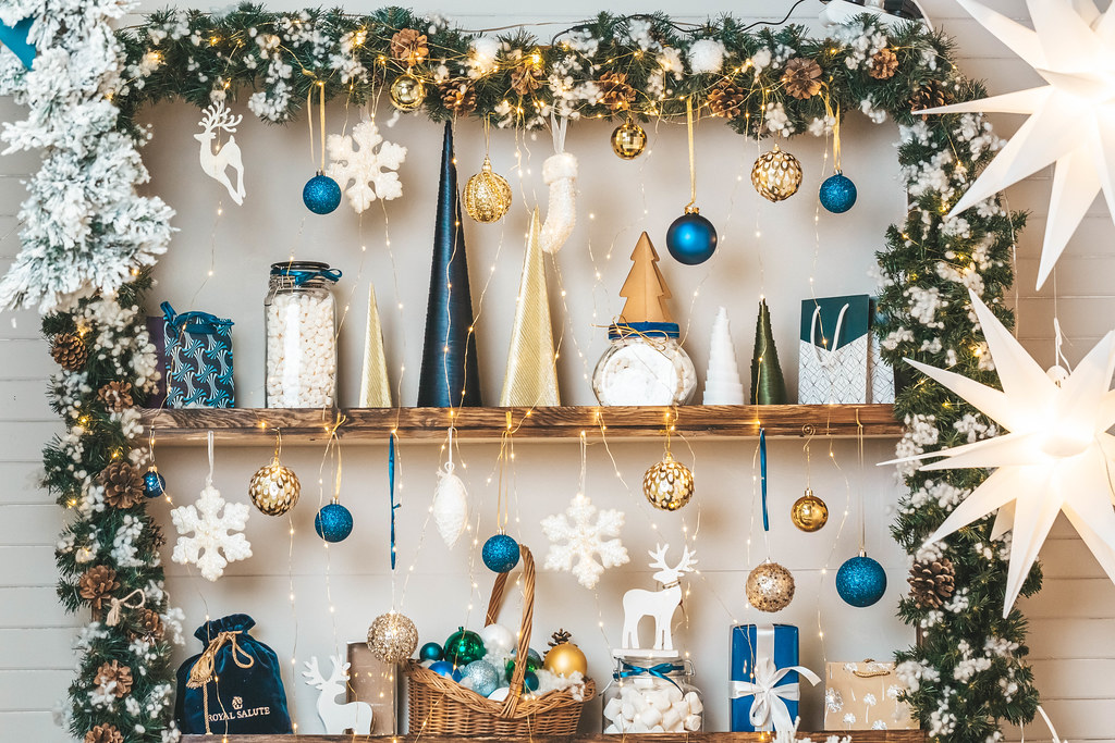 Xmas background decorated shelves with gifts, toy, marshmallow and glowing garland