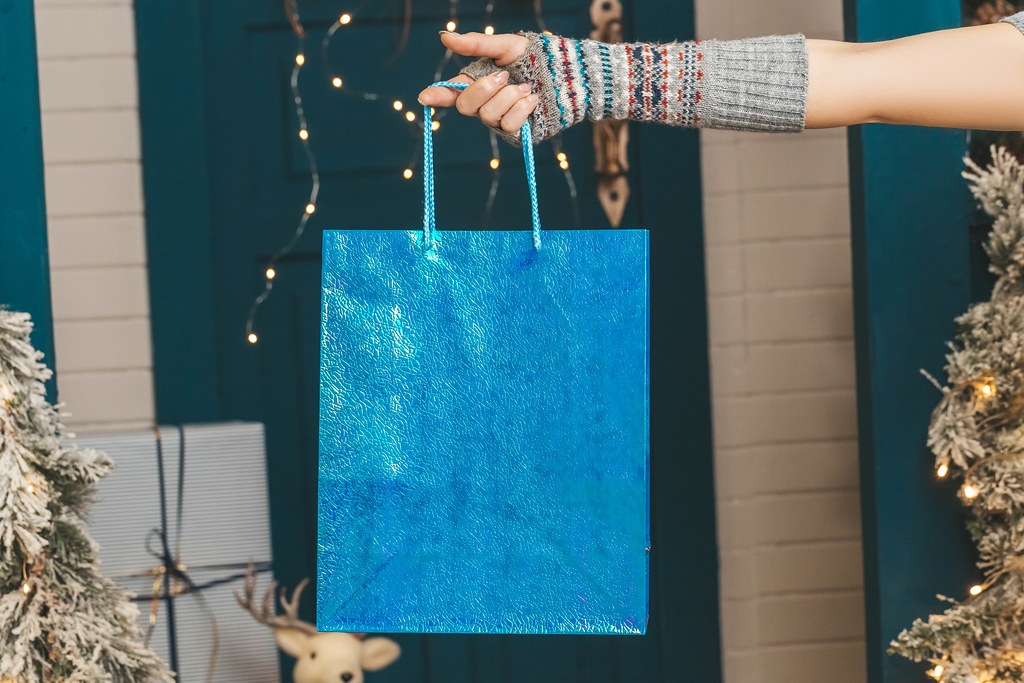 Blue gift bag in female hand, christmas concept