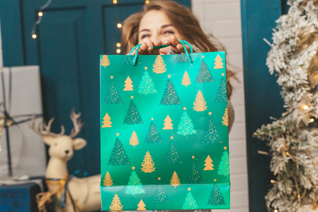 A woman holding a green gift bag in front of her