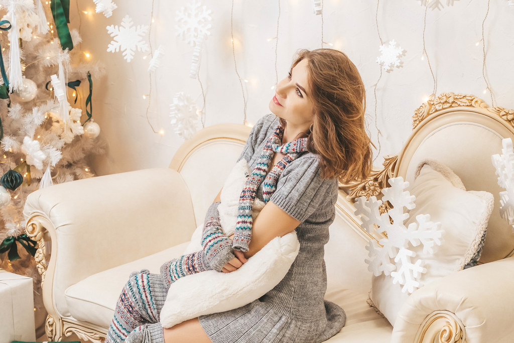 Girl sitting on the sofa in the christmas room and hugging a pillow