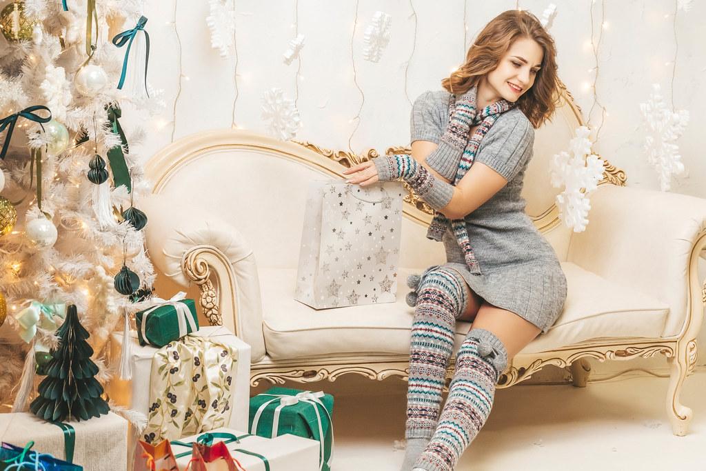 Happy girl sitting on sofa with christmas gift bag near christmas tree