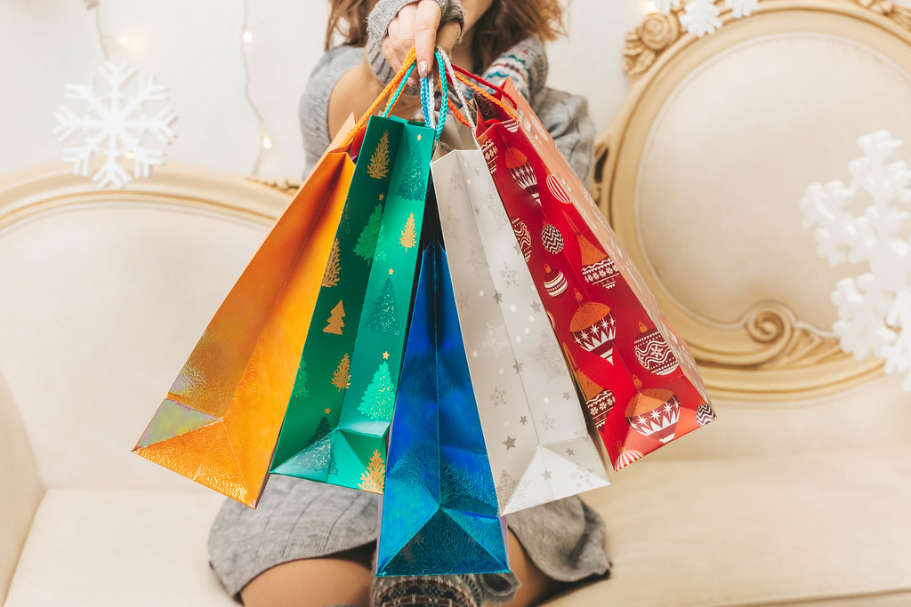 Multicolored bright gift bags in hand, close-up