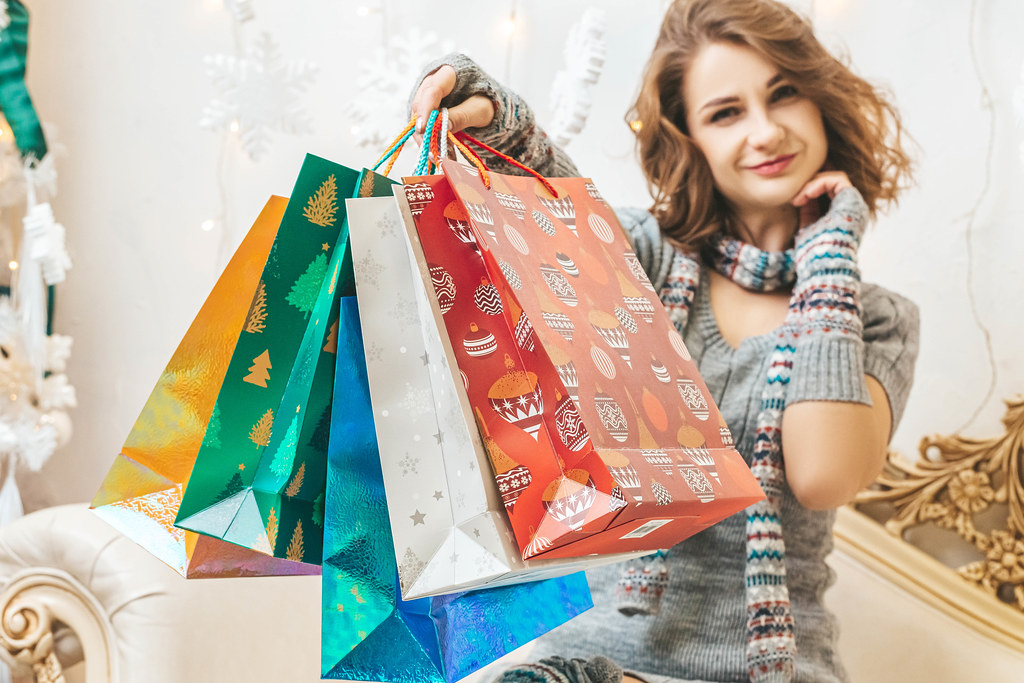 Christmas shopping, girl with many colorful gift bags