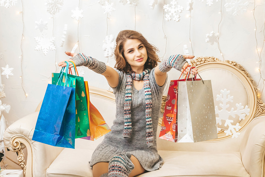 Woman smiling and holding a lot of shopping bags