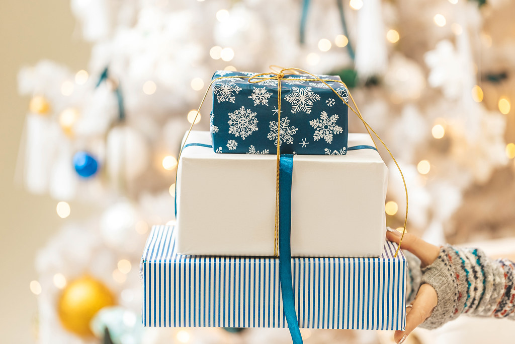 Blue and white gift boxes on blurred background of christmas tree with garlands