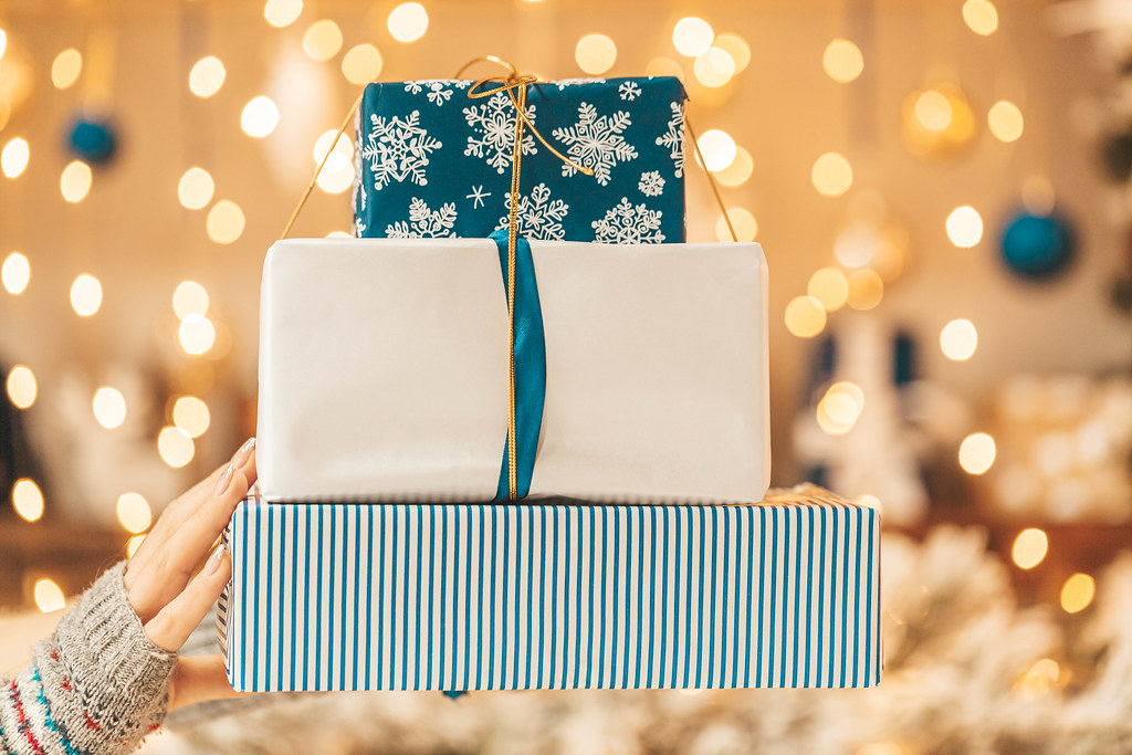 Stack of christmas gifts in female hand on golden bokeh background