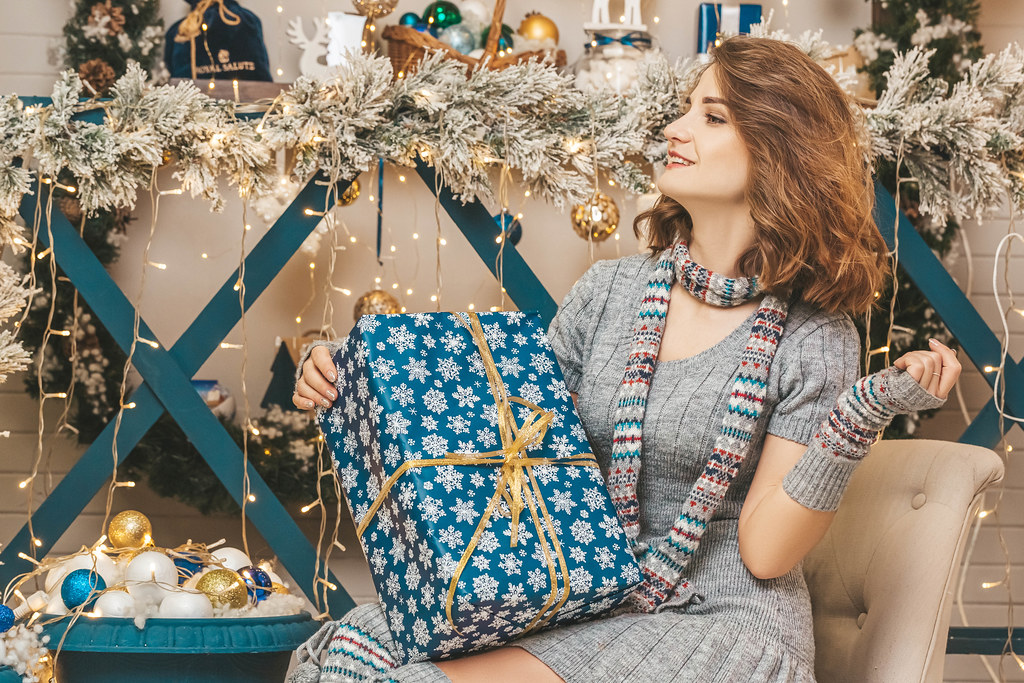 Girl sitting on an armchair in a christmas interior with a gift