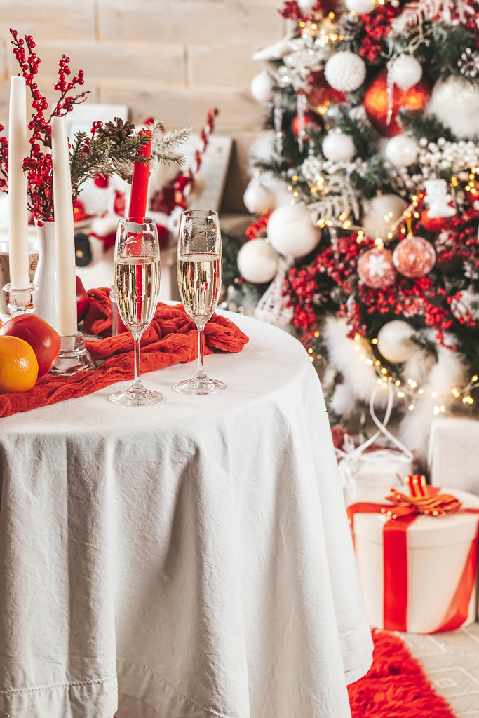 Christmas composition - two glasses with champagne on table near a christmas tree in beautifully decorated room
