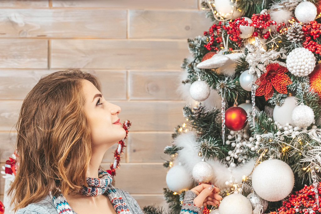 Portrait of a girl with a smile looks at the christmas tree