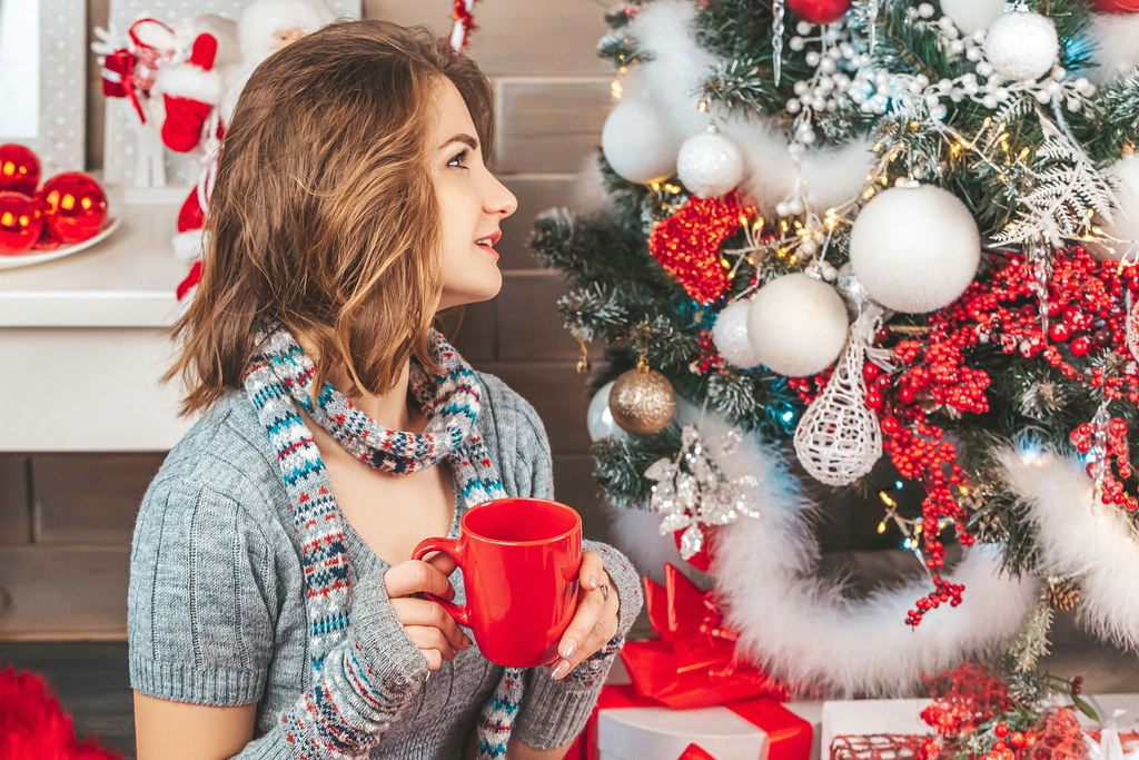 Girl with a red cup in her hands near the christmas tree