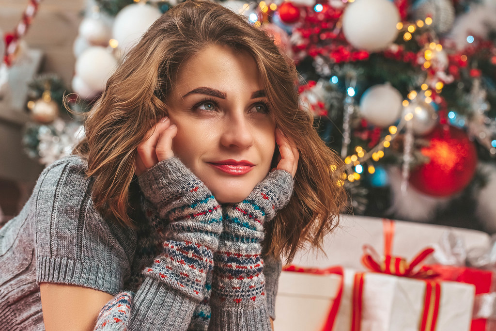 Portrait of a girl on a blurred background of a christmas tree and gifts