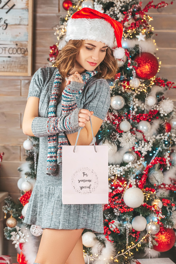 Beautiful girl in a knitted dress and santa hat with a gift bag in her hands