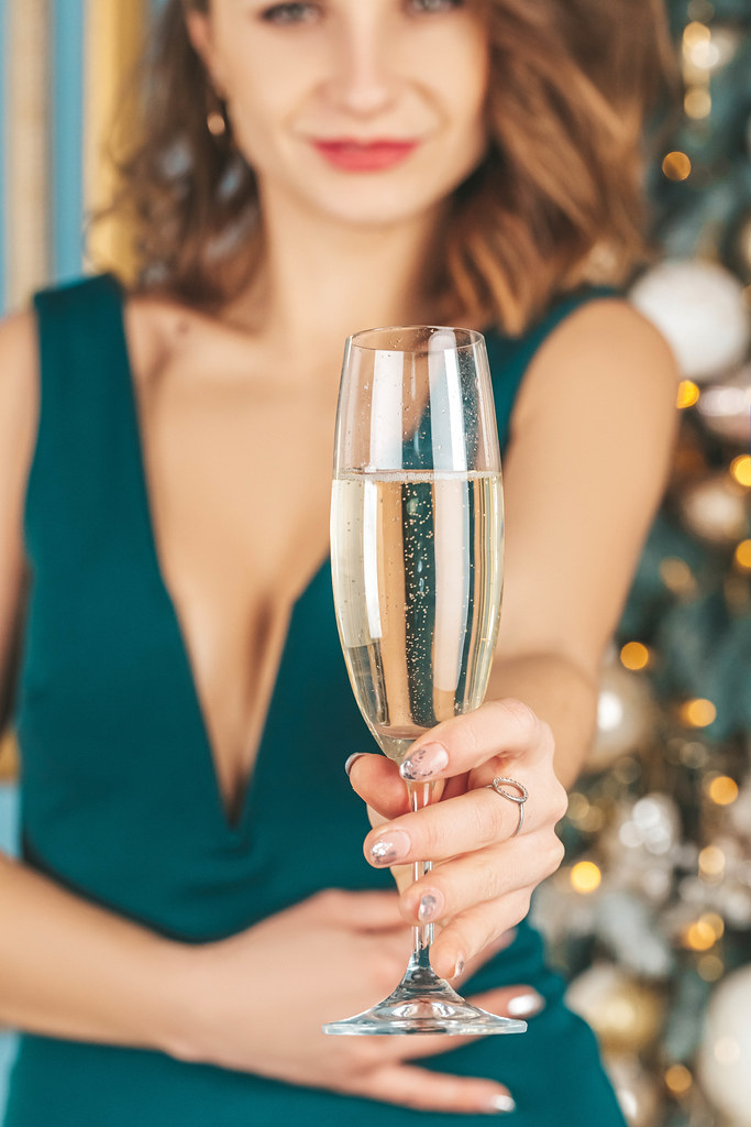Beautiful woman in an evening dress with a glass of champagne in her hand, close-up