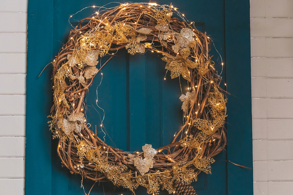Close-up of a christmas wreath with a garland on a blue door