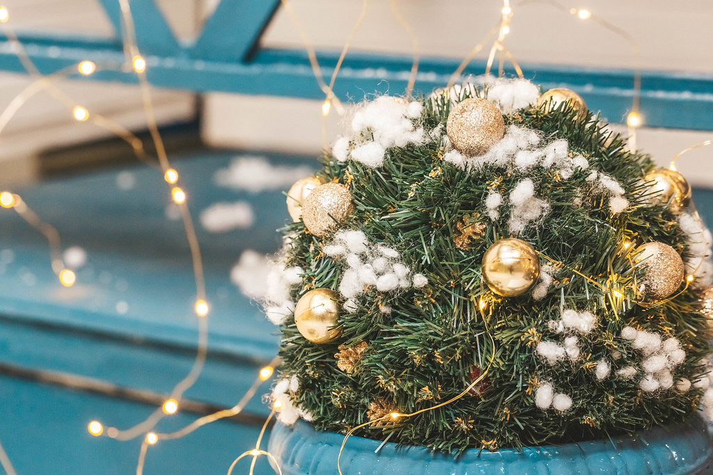 Christmas tree branches with balls, cones and garland, close-up