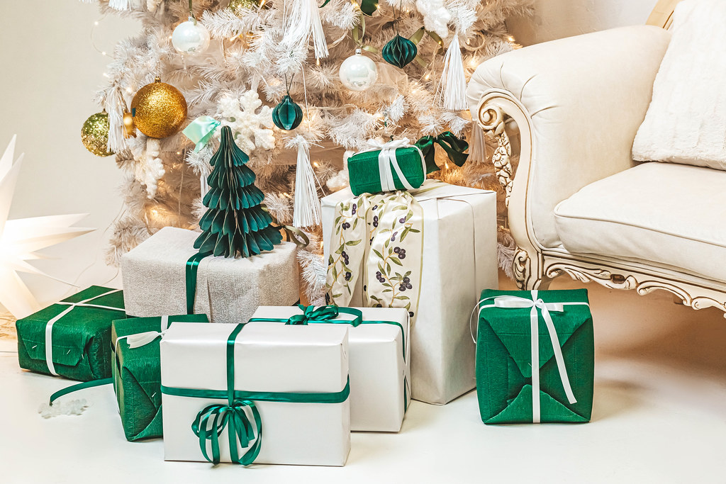 Many white and green presents on the floor under the tree