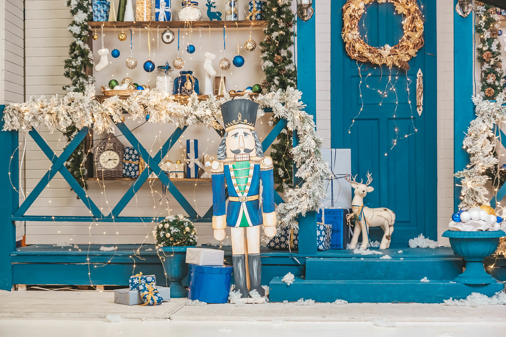 Figurine of a nutcracker near beautifully decorated steps and a door with a wreath