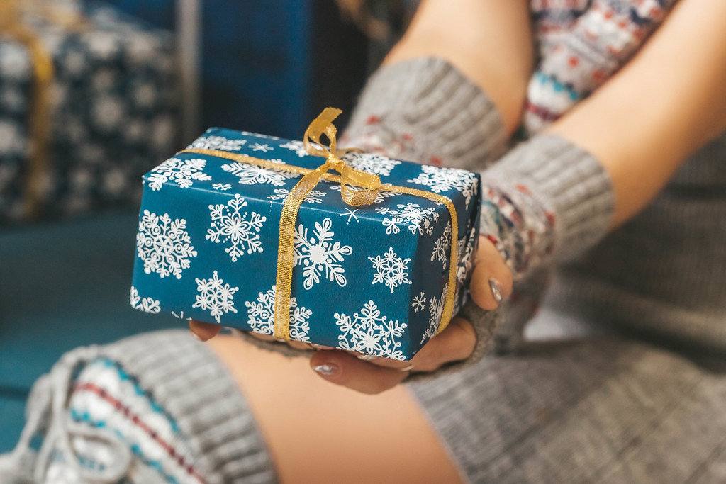 Blue gift box with gold ribbon in women's hands, close-up