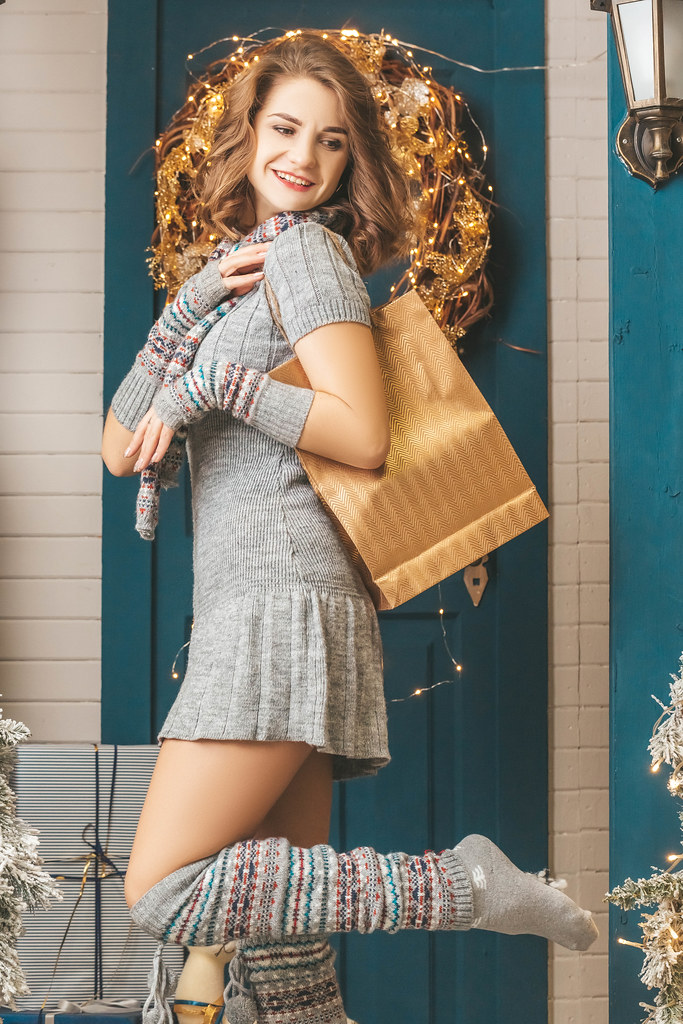 Beautiful girl with golden gift bag on her shoulder on christmas background