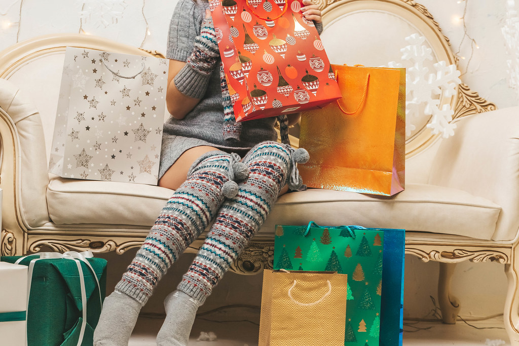 Girl sitting on the sofa with colorful bright gift bags
