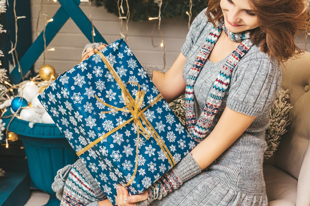 Close-up of a wrapped big christmas present in the hands of a girl sitting on an armchair