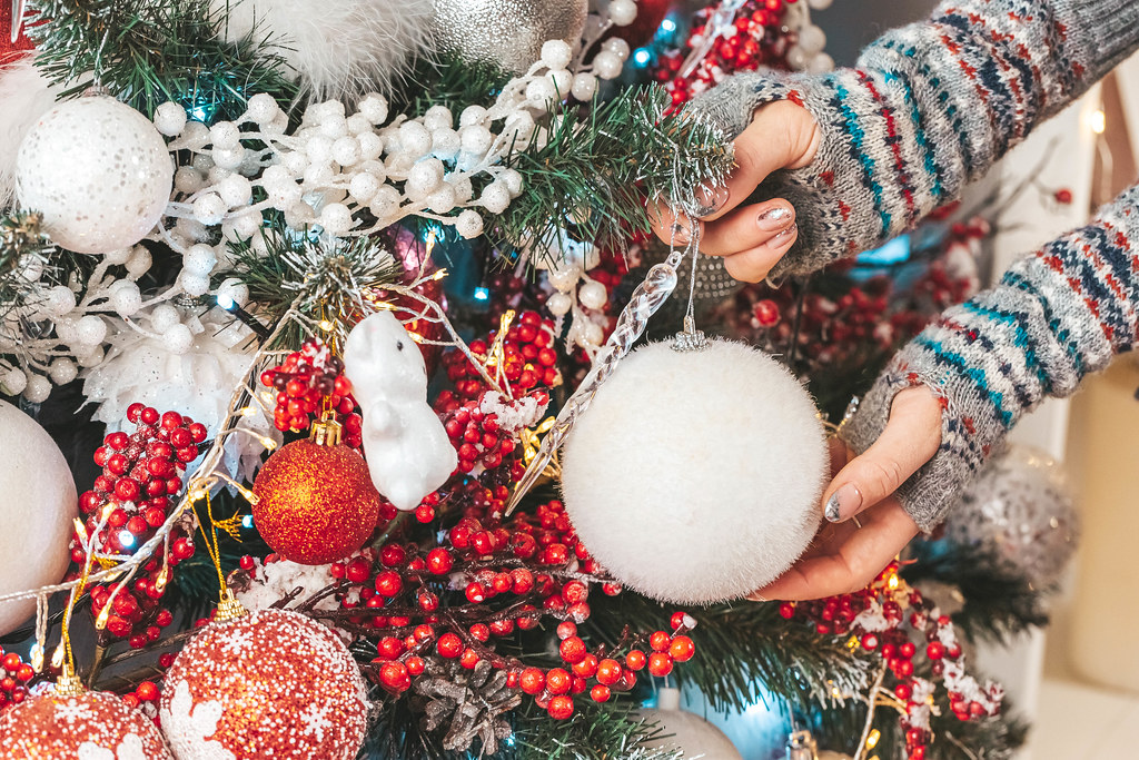 Decorated christmas tree and female hands, close-up