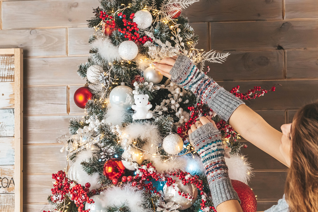Holiday background, a girl decorating a christmas tree in the living room